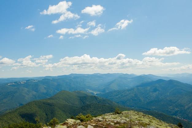 Красивый горный пейзаж с покрытыми лесом горными вершинами и облачным небом