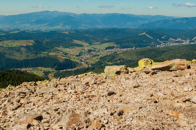 Красивый горный пейзаж, покрытые лесом горные вершины и пасмурное небо.