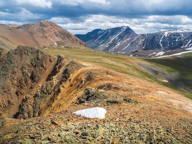 붉은 둥근 바위가 있는 아름다운 산 풍경. 큰 암석층, 다양한 암석층 및 토양층. 먼 산 고원.