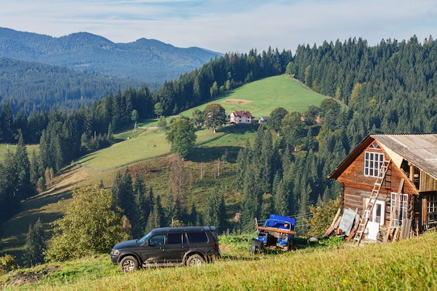 Beautiful mountain landscape with traditional wooden cabins on hill, houses and car in front