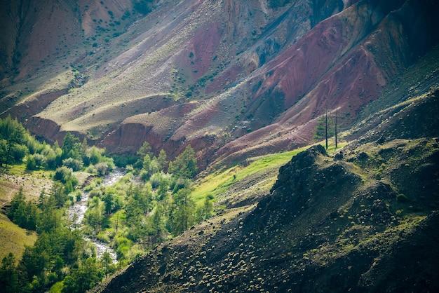 아름 다운 산 강과 여러 가지 빛깔의 점토 언덕 사이 계곡에 푸른 나무.