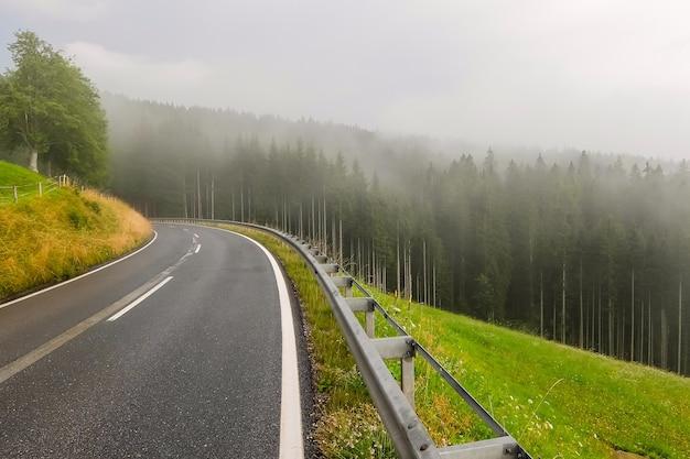 オーストリアの美しい山道。霧の森と背景の曇り空。