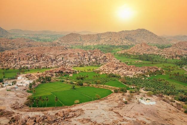 日没時のハンピ周辺の田んぼと丘の美しい山の岩の風景、カルナータカ州、インド