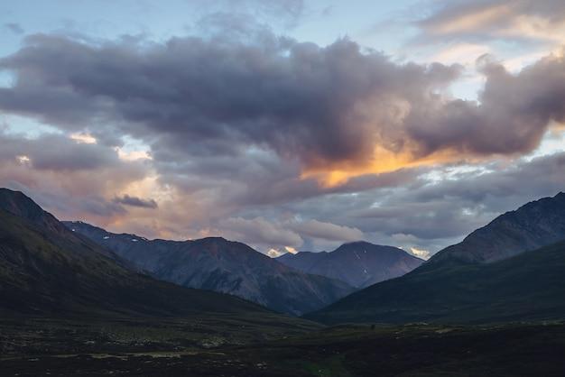 曇り空に金色の夜明けの光と美しい山の風景。夕焼け空に輝く色の風光明媚な山の風景。日の出の山のシルエット。空の日光を照らす金