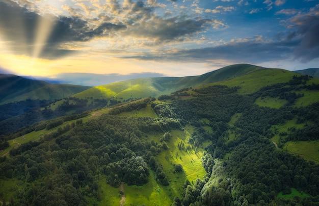 美しい山の夕日。美しい雲と輝く太陽の劇的な背景に雄大な山々