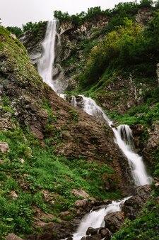 木々の間の美しい山の滝夏の自然背景垂直写真