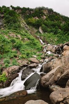 Красивый горный водопад среди деревьев летом естественный фон вертикальное фото