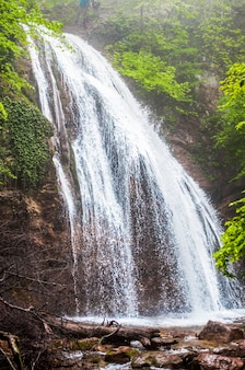 Красивый горный водопад протекает среди скал и окружен зелеными деревьями и кустами.