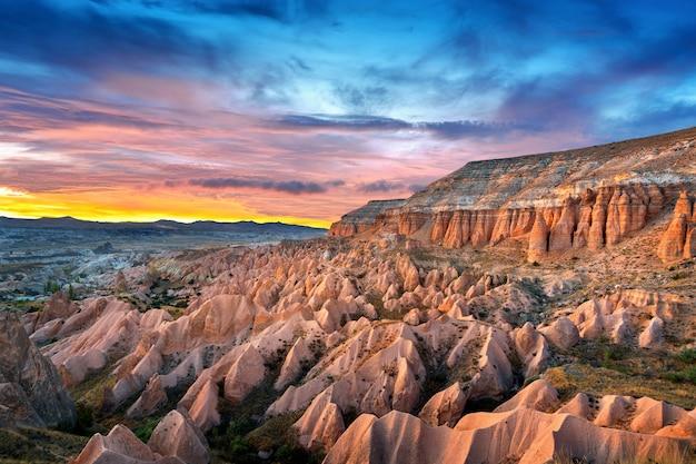 Belle montagne e valle rossa al tramonto a goreme, cappadocia in turchia.