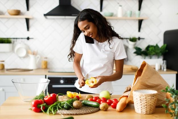 아름 다운 혹 백 혼혈 아 여자는 현대 부엌에 신선한 야채에서 식사를 요리 하 고 전화 통화