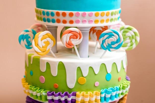 Красивый разноцветный детский торт из нескольких слоев, украшенный конфетами.