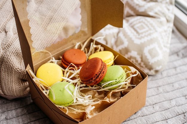 Beautiful multi-colored macaroons in a cardboard box
