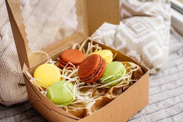 Beautiful multi-colored macaroons in a cardboard box