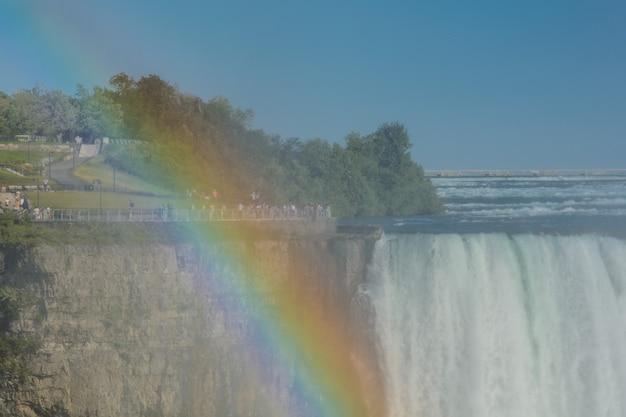 Красивая разноцветная радуга на фоне водопада. ниагарский водопад и радуга