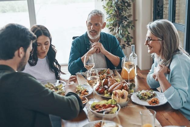 Красивая многопоколенная семья наслаждается вкусным ужином, сидя в современной квартире