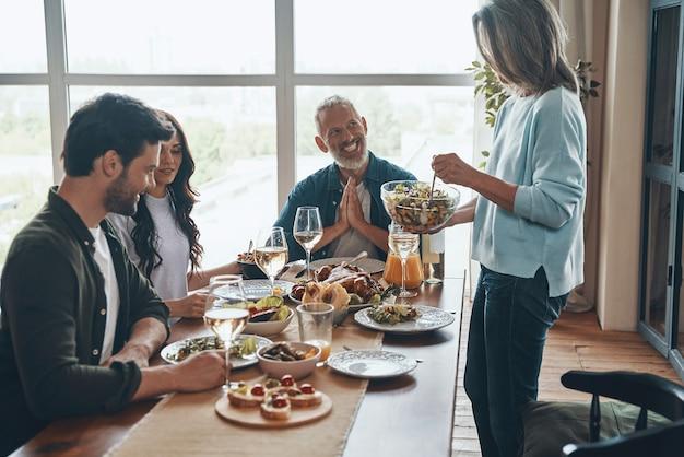 Красивая многопоколенная семья наслаждается ужином и улыбается, сидя в современной квартире