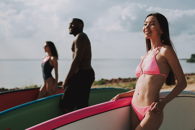 Beautiful multinational surfers stand on the beach