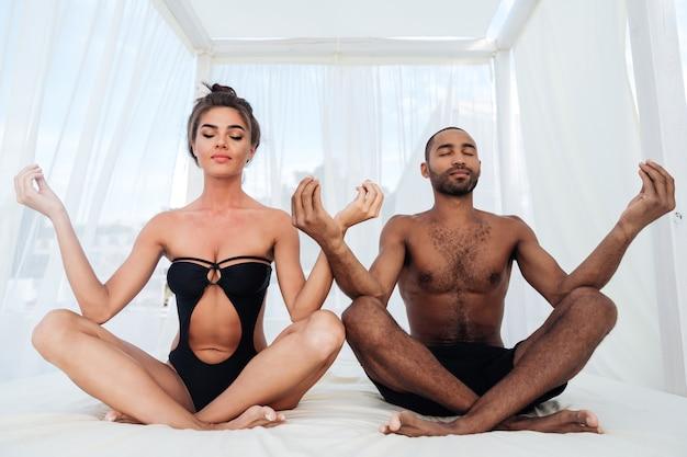 一緒に仲介し、ビーチのベッドで蓮華座に座っている美しい多民族のカップル