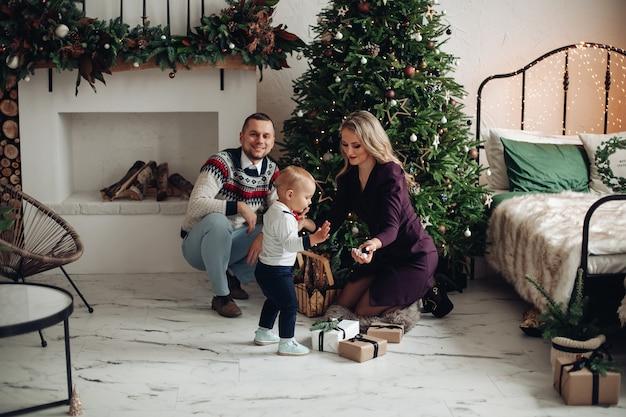 Прекрасные мама и папа украшают елку с любимым сыном дома