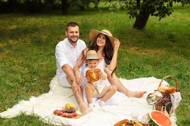 아름다운 엄마, 아빠, 그리고 그들의 귀여운 어린 아이가 함께 즐겁게 놀고 밖에서 웃는다