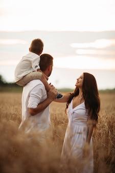 美しいお母さん、お父さんと彼らのかわいい小さな子供は一緒に楽しんで、外で微笑んでいます