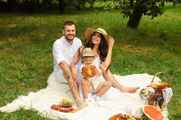 Beautiful mum, dad and their cute little child have fun together and smiles outside