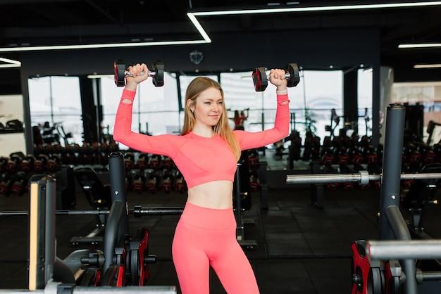 美しい筋肉にフィットする金髪の女性が運動し、ジムで筋肉を構築します