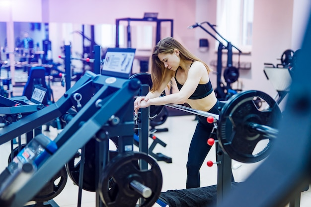 Beautiful muscular fitness woman in a black sporty clothes leaning on simulator with barbell at gym.
