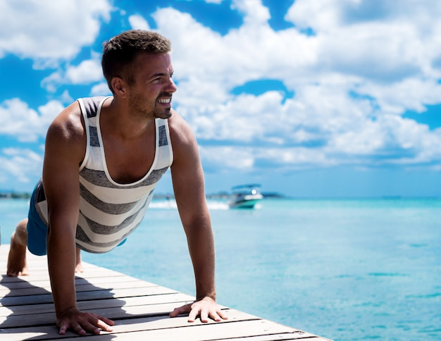 海で運動する美しい筋肉の男。夏の屋外フィットネスは、あなたをセクシーで日焼けさせます。