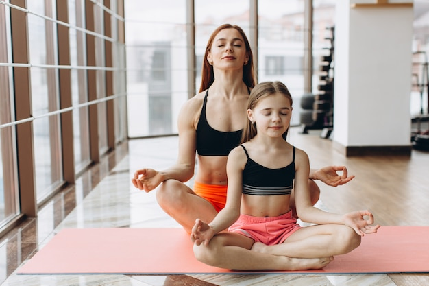 Beautiful muscular woman and her charming little daughter are smiling while doing yoga together at gym