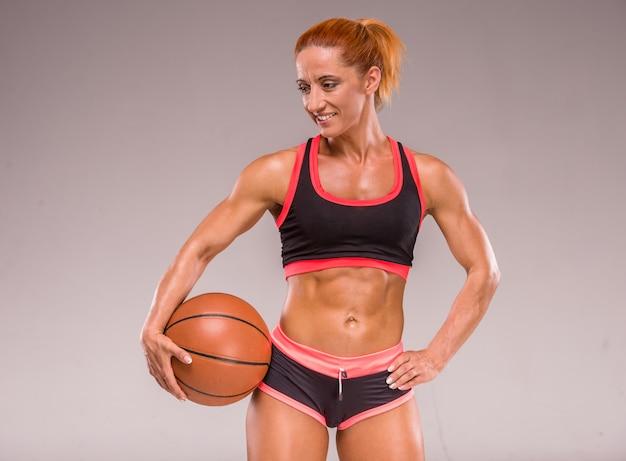 Beautiful muscular woman is holding a basket ball.