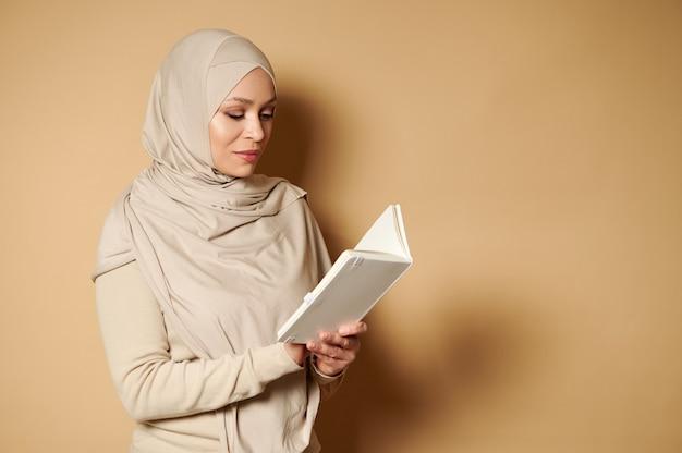コピースペースのあるベージュの表面で本を読んでヒジャーブと厳格なフォーマルな伝統的な衣装を身に着けている美しいイスラム教徒のアラビア語の女性