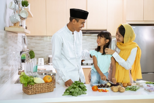 Beautiful muslim asian family cooking for iftar dinner together at home. couple with kid having fun making food in the kitchen