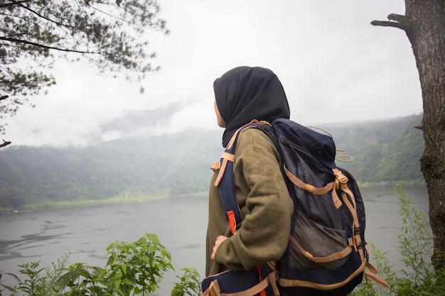 야생 산 호수 근처 놀라운 풍경을 즐기는 아름다운 이슬람 아시아 여성 등산객