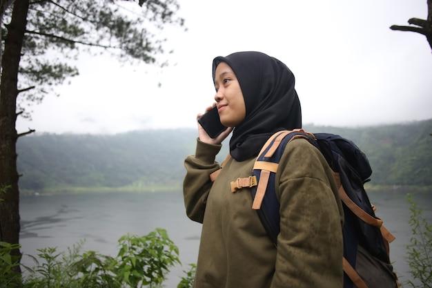 야생 산 호수 근처 전화로 말하는 아름 다운 이슬람 아시아 여자