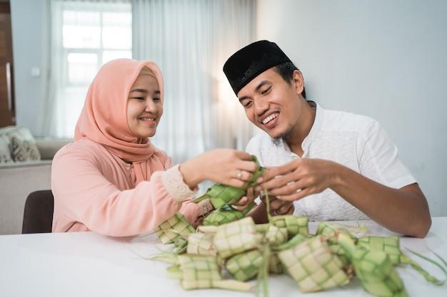 Красивая мусульманская пара азиатских готовит рисовый пирог кетупат дома с использованием пальмовых листьев