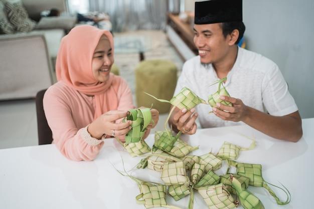 美丽的回教夫妇亚洲制作ketupat米糕在家使用棕榈叶