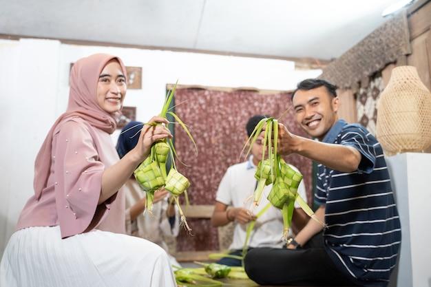 イードフィトルムバラクの伝統のためにヤシの葉を使用して自宅でケトゥパット餅を作る美しいイスラム教徒の家族と友人