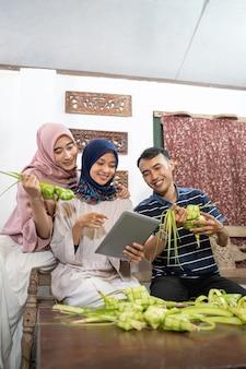 Красивая мусульманская семья и друг делают дома рисовый пирог кетупат из пальмовых листьев по традиции ид фитр мубарак
