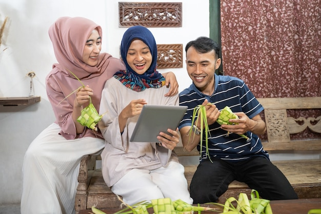 Beautiful muslim family and friend making ketupat rice cake at home using palm leaf for eid fitr mubarak tradition