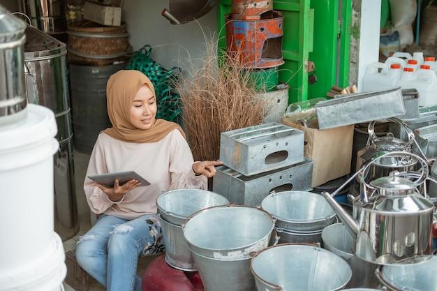 Красивая мусульманская женщина смотрит на экран планшета во время использования планшета в магазине