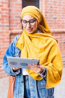 Beautiful muslim female student wearing bright yellow hijab holding tablet