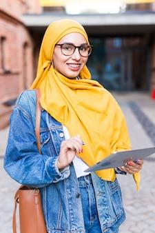 タブレットを持つ美しいイスラム教徒の女子学生