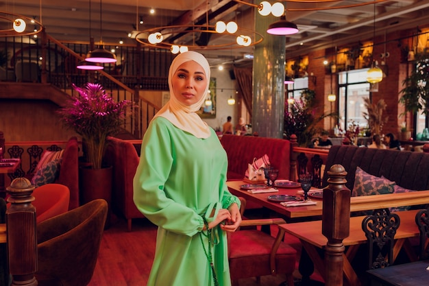Beautiful muslim girl in hijab smiling, waiting for her food in a restaurant.