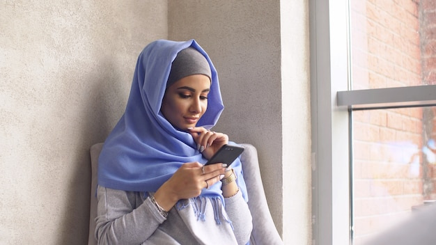 Beautiful muslim girl using smartphone in cafe. modern muslim woman and new technologies.