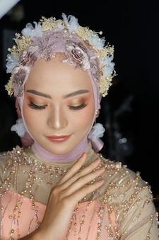 ヒジャーブと花と美しいイスラム教徒のインドネシアの女性 Premium写真