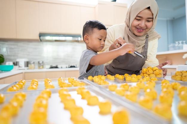 Красивая мама-мусульманка делает торт для ид мубарак с сыном дома вместе