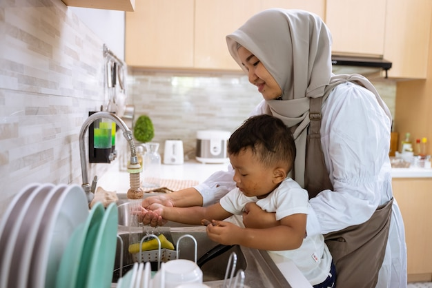 아름다운 이슬람 어머니는 부엌 싱크대에 그녀의 아들 손을 씻으십시오