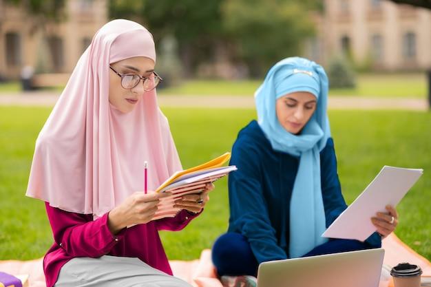 아름다운 이슬람 학생. 친구와 함께 공부하는 안경과 분홍색 히잡을 입고 아름다운 이슬람 학생
