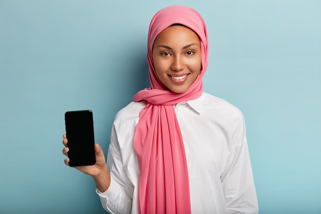Beautiful muslim woman advertises modern gadget, holds smart phone device with blank screen for your advertisement, wears traditional veil on head